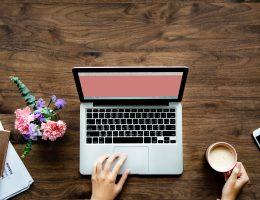 Laptop met roze scherm, koffie, notitieblok en bloemen